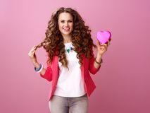 Smiling trendy woman isolated on pink background showing heart Royalty Free Stock Photography