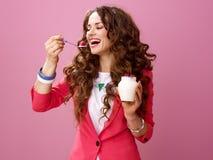 Smiling woman isolated on pink eating farm organic yogurt Royalty Free Stock Images