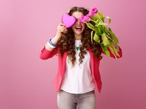 Woman hiding behind bouquet and heart shaped box of chocolates Royalty Free Stock Photos