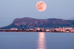 Pink Moon Rising. Above sea and a small mountain Stock Photo