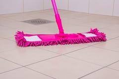 Pink mop cleaning tile floor in bathroom Stock Image