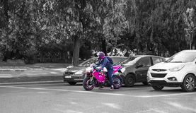 Pink motorcyclist standing out among balck and white cars Stock Photos