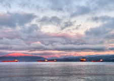 Sunrise With Transport Boats and Pink Mountains. Pink mountains at sunrise with tanker boats in foreground Royalty Free Stock Photo