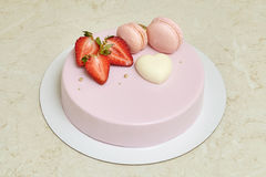Pink mousse cake mirror glaze, decorated with macarons and strawberry Stock Photography