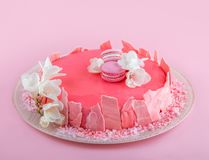 Pink mousse cake with mirror glaze decorated with macaroons, flowers for Happy Birthday on pink holiday background. Holiday cake. Celebration, close up royalty free stock photography
