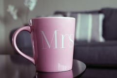 Mrs Wedding Mug. A pink Mrs mug on a coffee table in a living room royalty free stock image