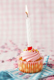 Pink muffin with candle. Close-up of a pink muffin with party candle. Studio shot Royalty Free Stock Photos