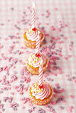 Pink muffins with candles. Close-up of pink muffins with party candles. Studio shot Stock Photos