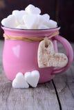 Pink mug with sugar hearts Royalty Free Stock Image