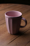 Pink mug on wooden table over grunge background Stock Photography