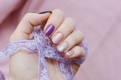 Pink nail art with glitter accent. Beautiful female hand with pink and purple manicure Stock Image