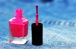 Pink nail lacquer on jeans background Royalty Free Stock Photo