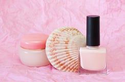 Pink nail polish. Pink nail polish and cream on a pink background Stock Photo