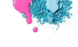 Pink nail polish spilled with broken blue eye-shadows. Beauty cosmetics creative texture set stock photo