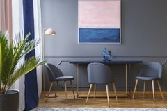 Pink and navy blue painting above table and grey chair in dining room interior. Real photo royalty free stock photography