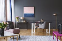 Pink and navy blue painting in grey living room interior with fl. Owers and armchair. Real photo royalty free stock photography