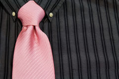 Pink necktie tied on black pinstriped shirt Stock Photos