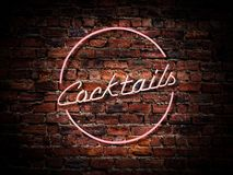 Pink Neon Cocktails Sign. A Pink Neon Cocktails Sign Against A Red Brick Wall Outside A Bar Or Pub royalty free stock photography