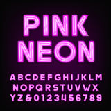 Pink neon tube alphabet font. Type letters and numbers on a dark background. Stock Photo