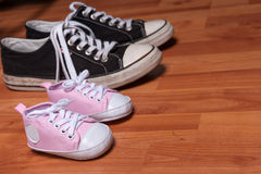 Pink newborn shoes and pair of adult sneakers Stock Photos
