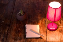 Pink night light and notebook with pencil. Night light on the desk. Top view royalty free stock images