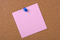Pink note with blue pin. On wood Stock Images