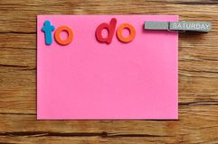 A pink note with the words to do and a peg attached with the word saturday on it. On a wooden background stock photo