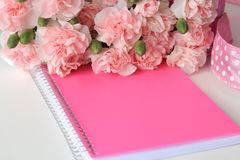 A pink notebook with a miniature beach watercolor painting. A white desktop with a pink notebook, flowers, and a dotted pink ribbon Stock Images