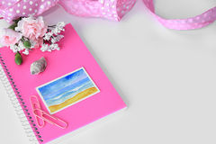 A pink notebook with a miniature beach watercolor painting. A white desktop with a pink notebook, a shell, paperclips, flowers, a beach watercolor painting, and Stock Photography