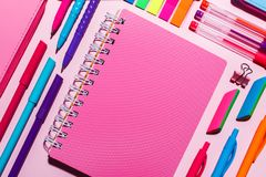 A pink notebook next to bright pens stock images