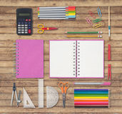 Pink notebook and school or office tools on wood background Stock Image