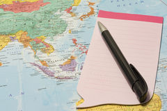 Pink notepad and pen on top of map Royalty Free Stock Photos