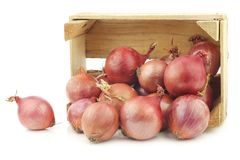 Pink onions in a wooden crate Royalty Free Stock Image