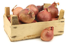 Pink onions in a wooden crate Royalty Free Stock Photo