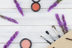 Pink and orange blush with make up brush in paper bag. And violet liatris flowers on white wood background with copy space royalty free stock photos