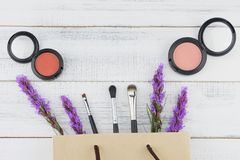 Pink and orange blush with make up brush in paper bag. And violet liatris flowers on white wood background with copy space stock image