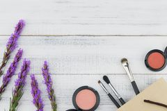 Pink and orange blush with make up brush in paper bag. And violet liatris flowers on white wood background with copy space royalty free stock photo