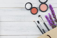 Pink and orange blush with make up brush. And violet liatris flowers on white wood background with copy space royalty free stock photos