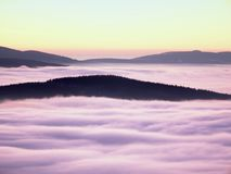 Pink orange sun rise above misty winter mountains. Shinning fog. Peaks of mountains above creamy mist in valley stock image
