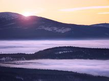 Pink orange sun rise above misty winter mountains Stock Photography