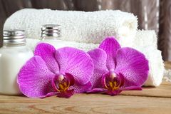 Pink orchid flowers near towels and white body lotion in the spa treatment room.  Royalty Free Stock Photos