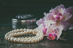 Pink orchid with a pearl necklace. Photo toned, selective focus. Royalty Free Stock Photos