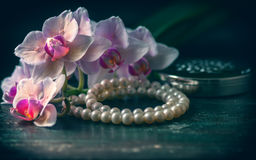 Pink orchid with a pearl necklace. Photo toned, selective focus. Stock Image