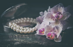 Pink orchid with a pearl necklace. Photo toned, selective focus. Royalty Free Stock Images