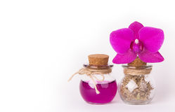 Pink orchid and two glass bottles on a white background. Spa concept. Cosmetic bottles. Ecological natural cosmetics. Copy space. Royalty Free Stock Photos