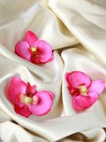 Pink orchids on a beige silk Stock Photos