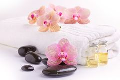 Pink orchids, moisturizing oils and spa stones on white. Towel royalty free stock image