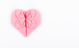 Pink origami heart on a white background. A valentine made of paper. Copy space Royalty Free Stock Photos