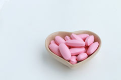 Pink oval pills in the cup shape of heart Royalty Free Stock Photo