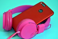 Pink overhead external large headphones and a phone with a dual camera in a red protective case. Closeup on a blue background. royalty free stock photo